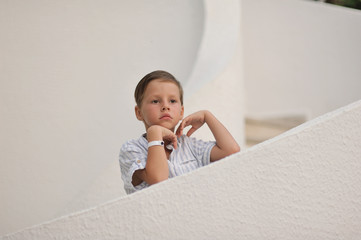 cute little boy in white shirt standing on white stairs