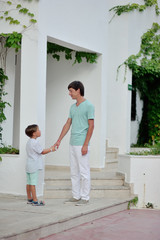father and son standing near a house with a white wall of a summ