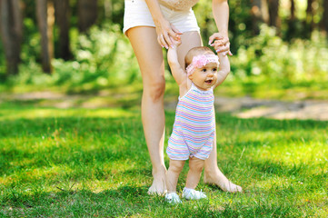 Mother teaching baby to walk in the park