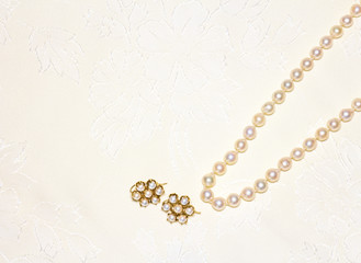 Elegant pearl necklace,matching earrings on cloth