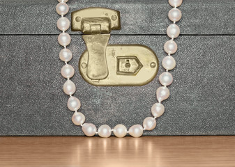 Pearl necklace over vintage jewelry box on wood grain surface