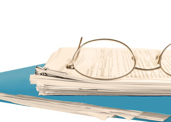 Reading glasses on stack of papers held by bulldog paper clip