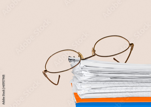 Reading glasses,folders,stack papers held by bulldog paper clip