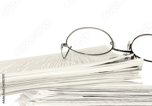 Reading glasses,stack of papers held by bulldog paper clip