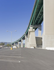Empty parking lot under concrete bridge,blue sky,vertical view