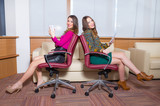 Portrait of two attractive girls posing in office