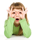 Astonished little girl is showing glasses gesture