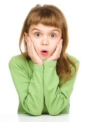 Little girl is holding her face in astonishment