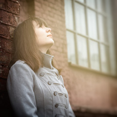 young girl standing near a brick wall and looking up