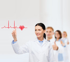 smiling female doctor pointing to cardiogram