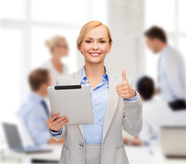 smiling woman with tablet pc showing thumbs up