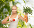 smiling woman holding heart symbol and carrots