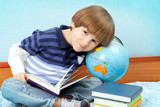 Small boy sit with books and globe