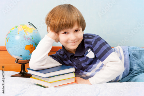 The boy lean elbow on stack of books