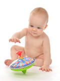 Infant child baby boy toddler playing with whirligig toy on a fl