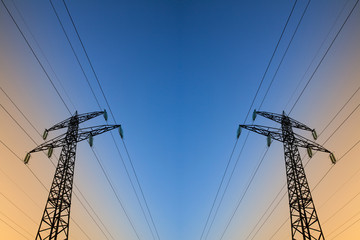 Electric power lines against blue and yellow sky