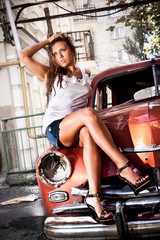 Sexy woman sitting on hood of old rusty red car