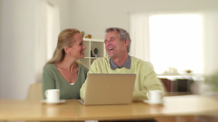 Senior couple sitting at desk laughing