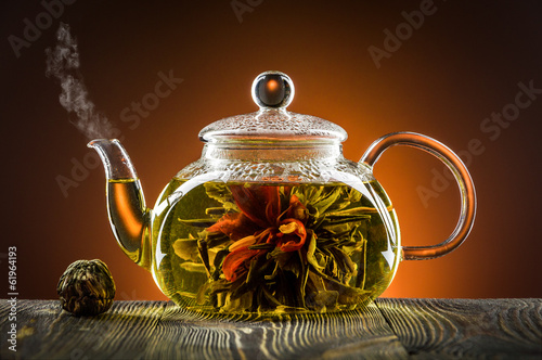 Fototapeta Glass teapot with blooming tea flower on wooden table