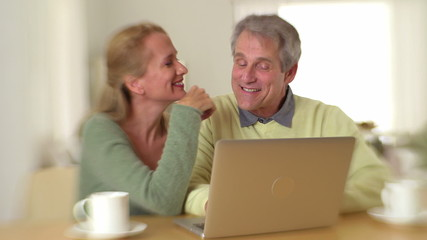 Senior couple happily using laptop