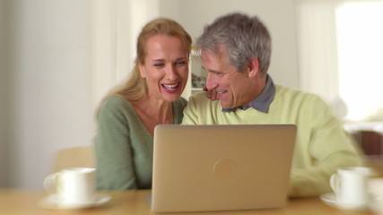 Mature couple smiling and talking with laptop