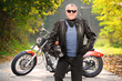 Mature biker in leather jacket standing in front of his chopper