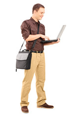 Full length portrait of a young man working on laptop