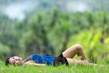 Young Filipina woman relaxing on green grass