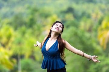 Beautiful young woman embracing the sun