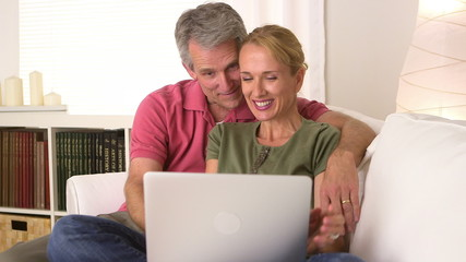 Senior couple using laptop  on the couch