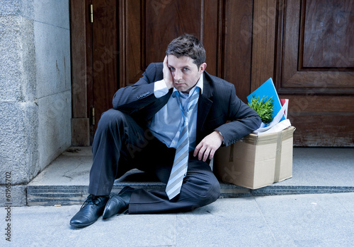 frustrated business man on street fired with cardboard box