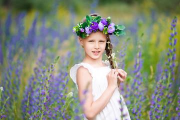 Girl in a white dress on a flower meadow