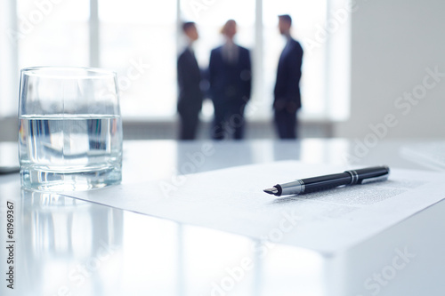 Pen on document and glass of water