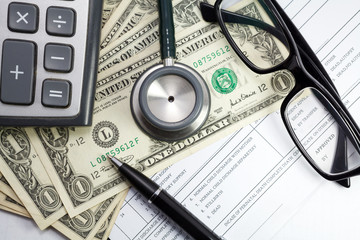 Pen stethoscope glasses and dollar on blank Patient information