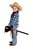 adorable young cowboy riding a stick horse werious face