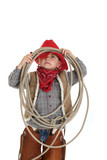 Funny pose of a young cowboy holding a rope