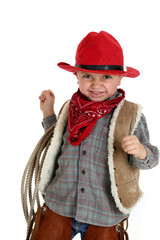 cute toddler cowboy smiling holding a rope wearing a red hat