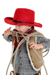Cute young cowboy toddler biting a rope wearing red hat