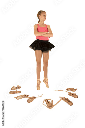 Young girl ballerina surrounded by ballet shoes arms folded