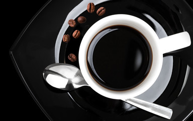 Coffee in white cup on black saucer,  top view