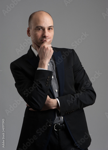 handsome man in black suit thinking