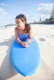 Cute young girl lying on surfboard