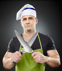 Man cook holding two big sharp knives