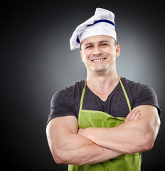Smiling muscular man cook with arms folded