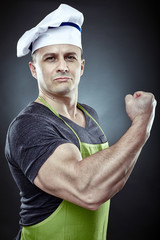 Muscular man cook displaying his biceps