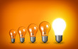 Row of light bulbs.Idea concept on orange background.