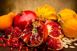 pumpkin and red pomegranate on fabric background