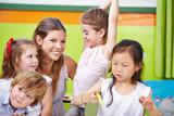 Fototapety Lächelnde Erzieherin mit Kindern im Kindergarten