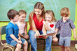 Leinwanddruck Bild - Kinder mit Erzieher lesen Buch im Kindergarten