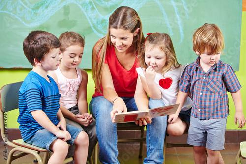 Leinwanddruck Bild Kinder mit Erzieher lesen Buch im Kindergarten